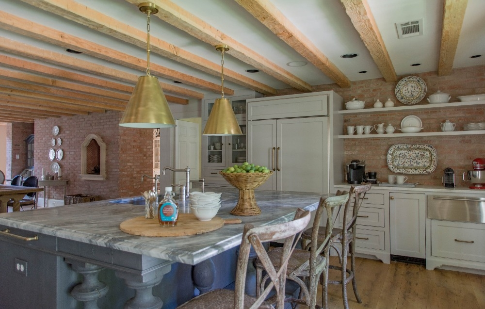 Chef's kitchen is cozy and warm, with Pecky Cypress beams, custom millwork and gray center island. This house was inspired by the work of A. Hays Town and designed by Curated by Kristin Mullen.