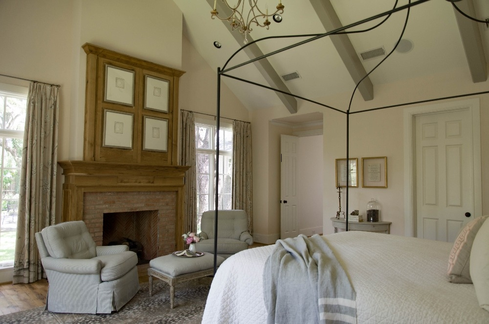 Southern style master bedroom with Tara Shaw bed, beautiful beams and custom millwork fireplace. Curated by Kristin Mullen.
