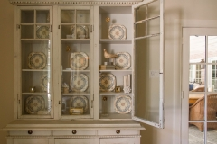 Antique China cabinet filled with curiosities and decor. Curated by Kristin Mullen.