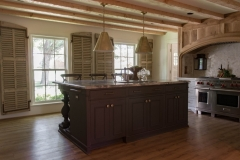 Chef's kitchen features a custom hood over the range to compliment the Pecky Cypress beams. Curated by Kristin Mullen.