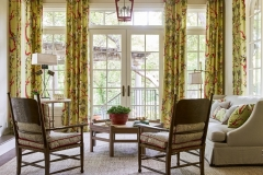 Garden inspired sunroom / reading room drenched in natural light. Bright green draperies and red pendant lantern add pops of color throughout. Curated by Kristin Mullen