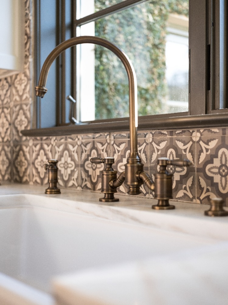 Farm-style kitchen sink with stunning hardware and a hand-painted antique tile backsplash. Curated by Kristin Mullen and Photography by Marc Montoya of Billy Surface.