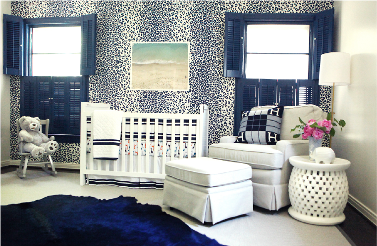 This nursery we designed features a leopard print accent wall, rich navy blue plantation shutters and cow hide rug and white furniture. Curated by Kristin Mullen