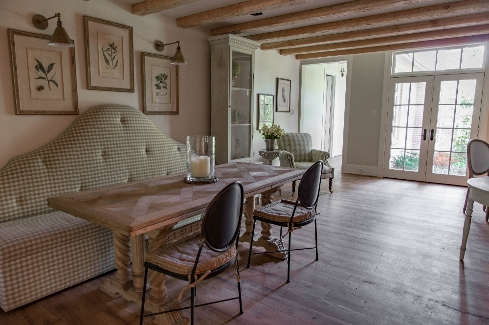Breakfast room featuring Pecky Cypress ceiling beams, an elevated fireplace, and a custom banquette in pale green gingham fabric. Curated by Kristin Mullen.