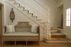 Foyer features a stunning staircase, accented by a whimsical Swedish antique bench. Curated by Kristin Mullen.