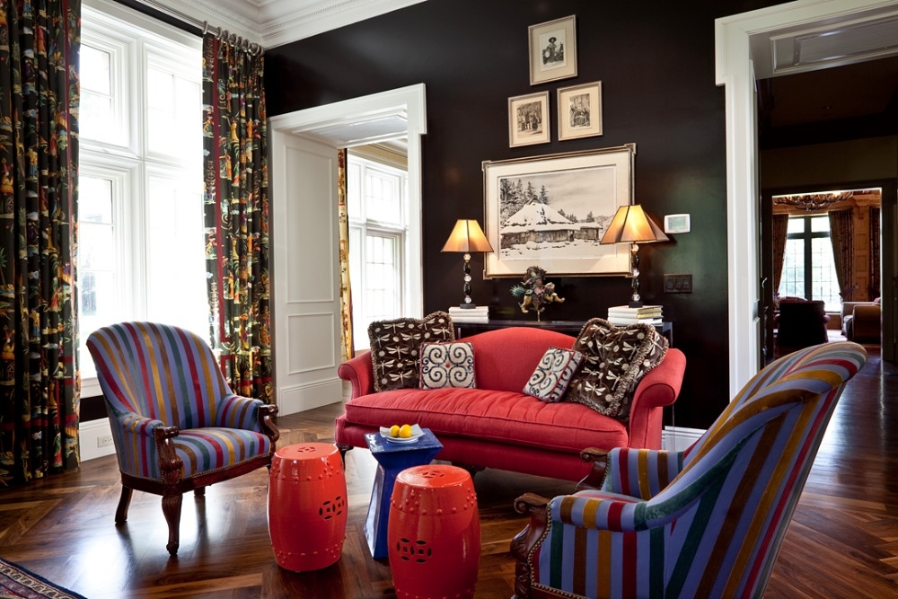 Living room at Meadowood is truly an amalgamation of pieces from our travels around the world. I chose a black-brown lacquer for the walls, and let the colorful fabrics do the talking. In terms of furniture layout, a tall table below the central chandelier breaks the room into two seating areas, both featuring a dramatic, red sofa.