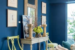 Detail shot of the Kristin Mullen Designs' vignette for Thrift Studio 2018 benefitting Dwell With Dignity. This room features a rich blue paint color, garden inspired accents and lime green touches. Antique mirror, lime green side chair and hydrangeas.
