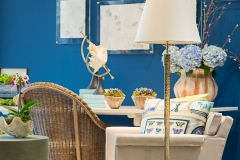 Detail shot of the Kristin Mullen Designs vignette for Thrift Studio 2018 benefitting Dwell With Dignity. This room features a rich blue paint color, garden inspired accents and lime green touches. The desk features natural curiosities, hydrangeas and painted butterfly watercolor art in lucite.