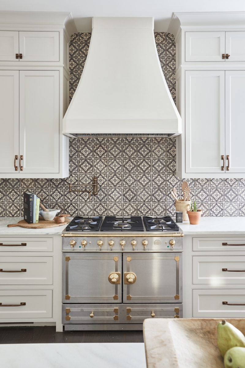 La Cornue range in silver is contrasted by a custom hood and hand painted antique tile backsplash. Curated by Kristin Mullen and Photography by Marc Montoya of Billy Surface