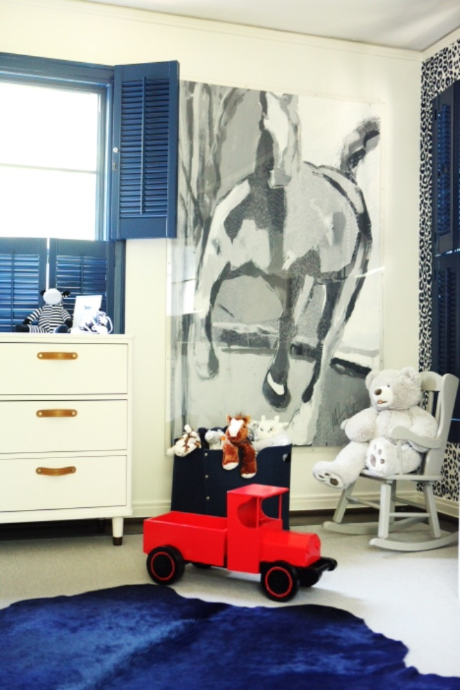 A bright blue cowhide is complimented by a toy truck in the blue nursery for this sweet baby boy. We chose simple, white furniture to contrast the rich navy blue details and cheetah print accent wall. Curated by Kristin Mullen
