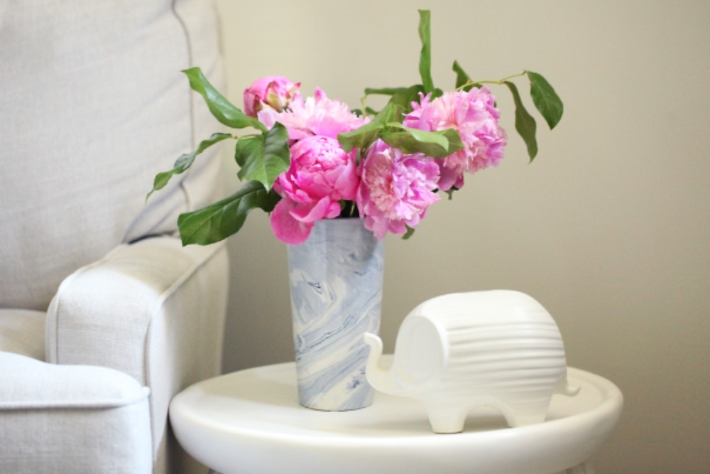 White garden stool side table in the nursery is accented by decorative pieces from Mecox and gorgeous fresh peonies. Curated by Kristin Mullen