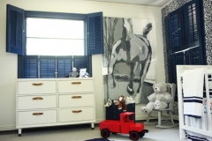 Baby nursery features rich blue plantation shutters, a one of kind art installation and bright white furniture. Curated by Kristin Mullen