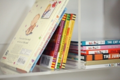 Lucite bookshelves in the nursery to showcase colorful baby books. Curated by Kristin Mullen